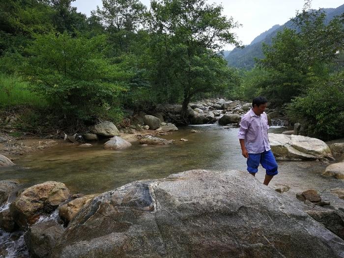 2017年8月23日,杨习伦蹚水前往养鸡场。新华社记者陈诺摄
